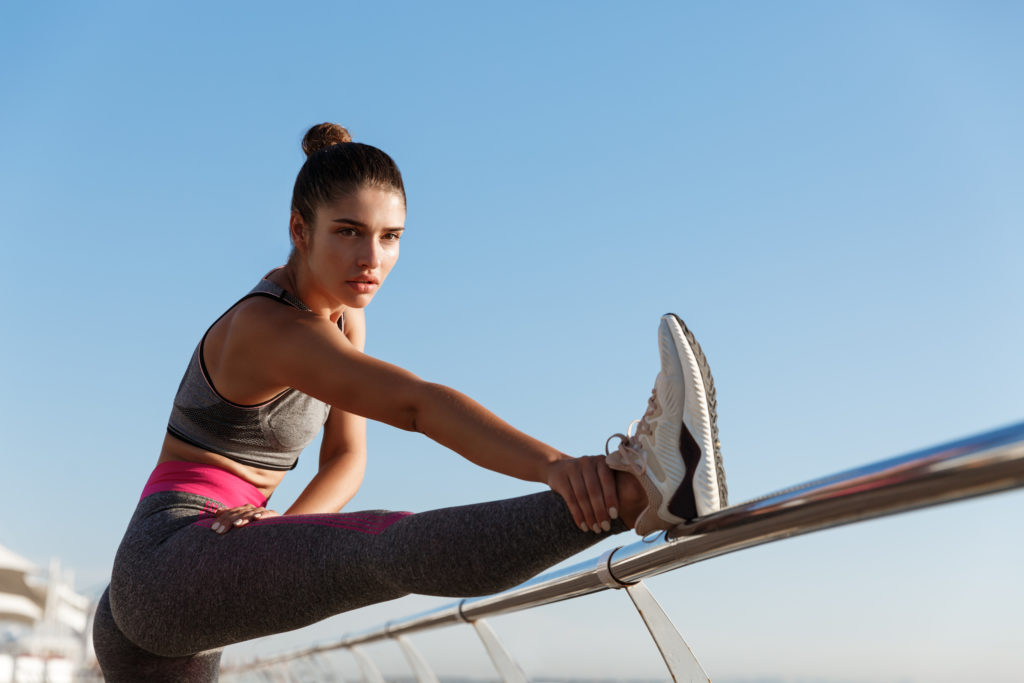 Image of attractive fit fitness girl workout on a pier. Sportswoman stretching legs and warming-up before jogging training on the seaside promenade.